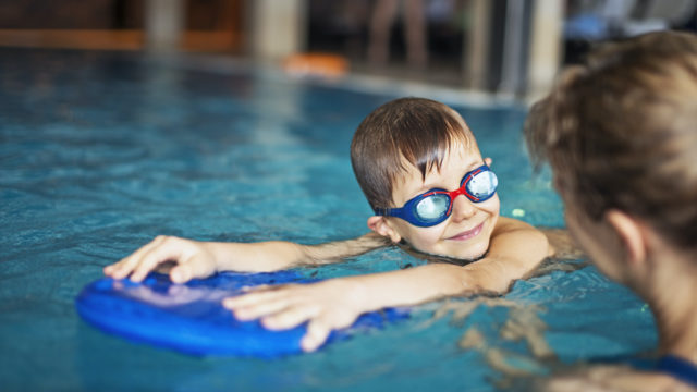 Happy Little Boy During Swimming Lesson Smiles At His Mother. The Boy Is Aged 6 And Is Wearing Swimming Goggles. The Boy Is Using A Kickboard.
